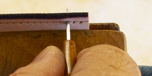 Défonce du cuir avec l'alène.