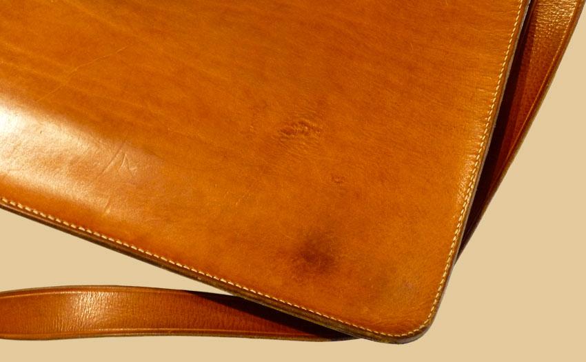 Vue de dos, la besace en cuir naturel a un cachet unique avec lapatine du temps.