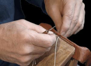 Couture d'élément de selle moto à la main.
